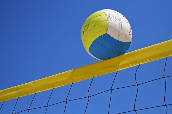 white yellow blue volleyball on top of net