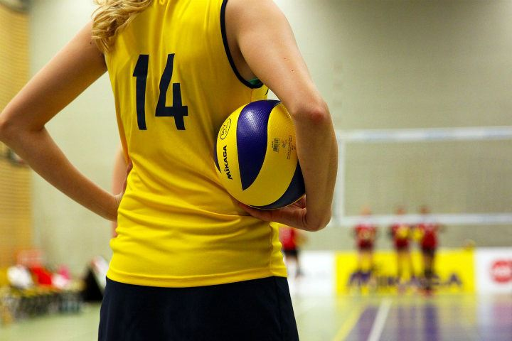 volleyball girl in yellow shirt holding ball