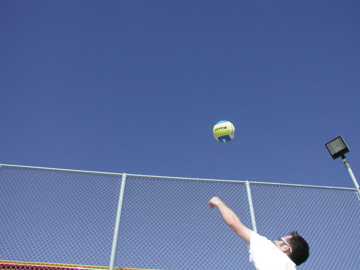 volleyball player tosses ball for serve