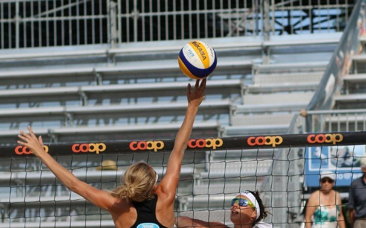 girl hitting a volleyball above net outdoors